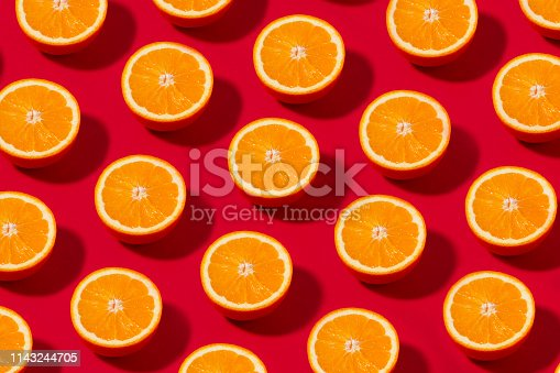 Fruit pattern with half slices of orange fruit on red background