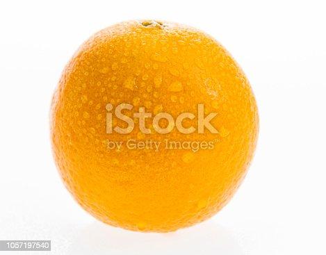 Orange fruit with drops on white background.