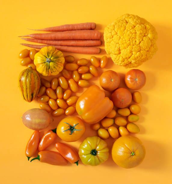 fruits et légumes oranges - fond couleur uni photos et images de collection