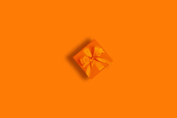 Orange gift box on orange background stock photo