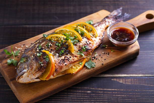 Pescado de besugo de jengibre naranja, espolvoreado con semillas de sésamo y cilantro en la tabla de servir. Salsa de naranja de soja - foto de stock