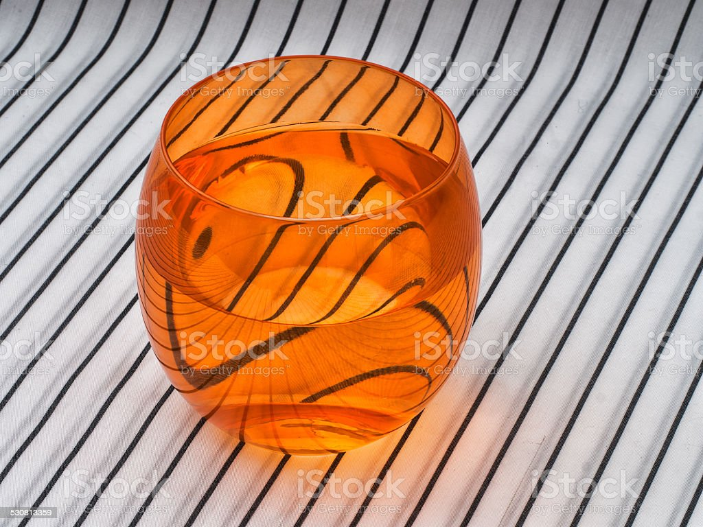 Orange glass of water on striped pattern background. stock photo