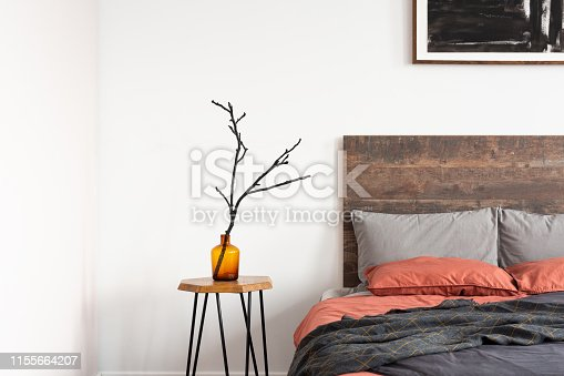 Orange glass vase with a tree branch standing on the wooden table next to bed with colorful sheets