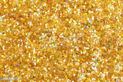 886746424 istock photo Orange glitter texture Christmas background. Bright golden glitter. 1056709672