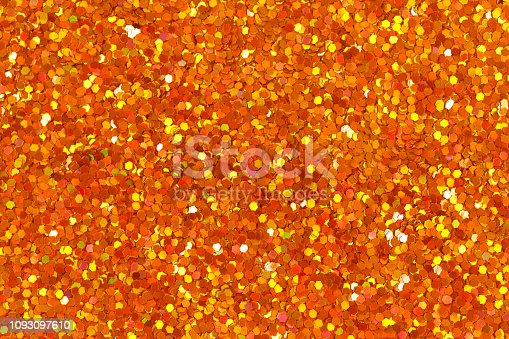 886746424 istock photo Orange glittering foil leaf shiny wrapping paper glitter texture background for Christmas holiday. 1093097610