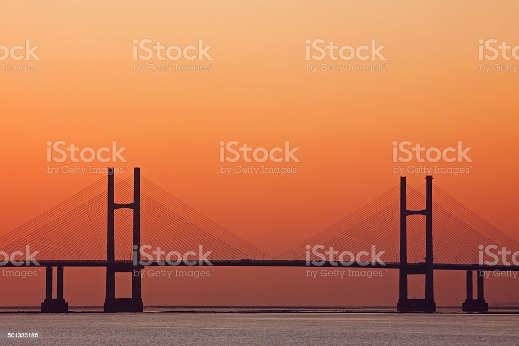 Orange glow at sunset behind the Severn road bridge UK stock photo