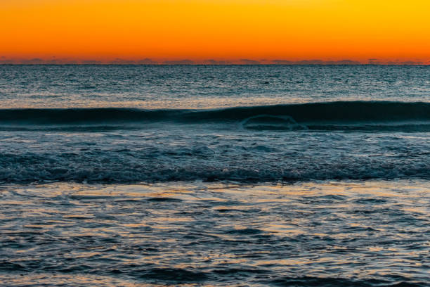 orange glowing sky over blue ocean water at dawn stock photo