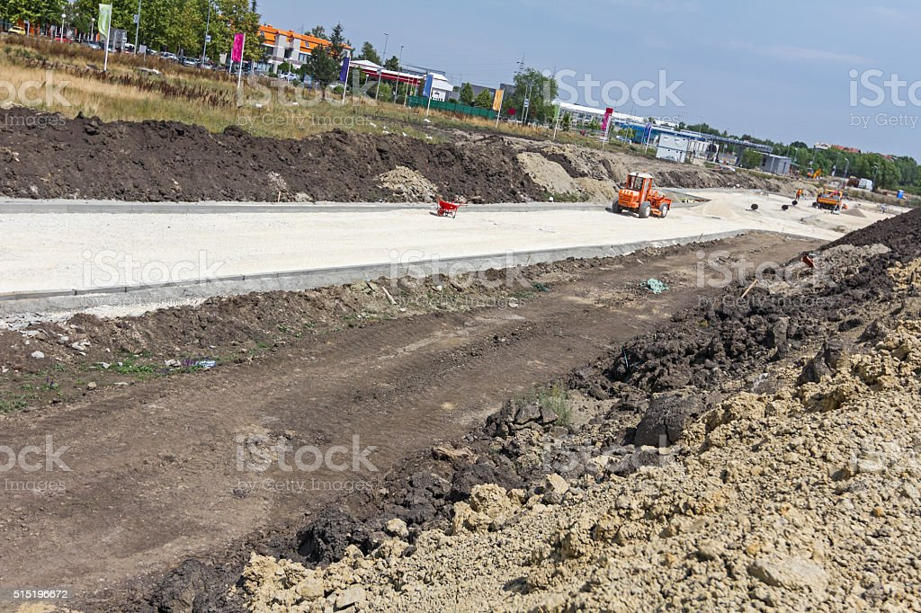 Orange grader is leveling the gravel ground at building site. stock photo