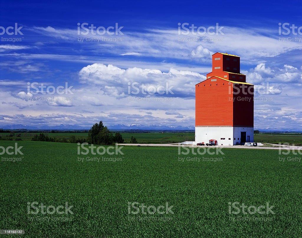 Orange grain elevator in green fields royalty-free stock photo