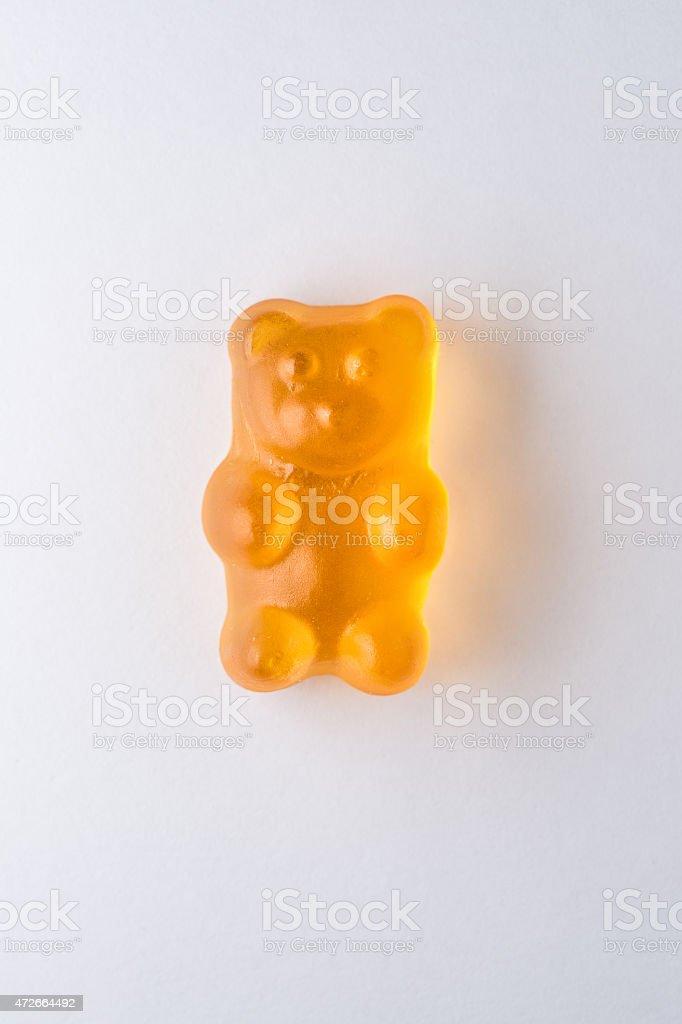 Orange gummy bear candy on white paper stock photo