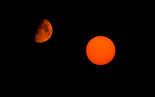 Taken in Northern California in late August 2017, when a wildfire gave the moon and the sun a dark orange hue. Compilation of two separate images taken on the same day.