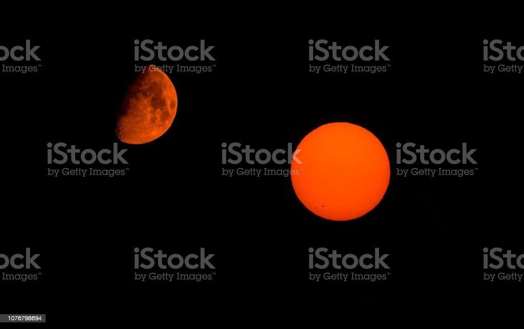 Orange half moon and sun against a black sky stock photo
