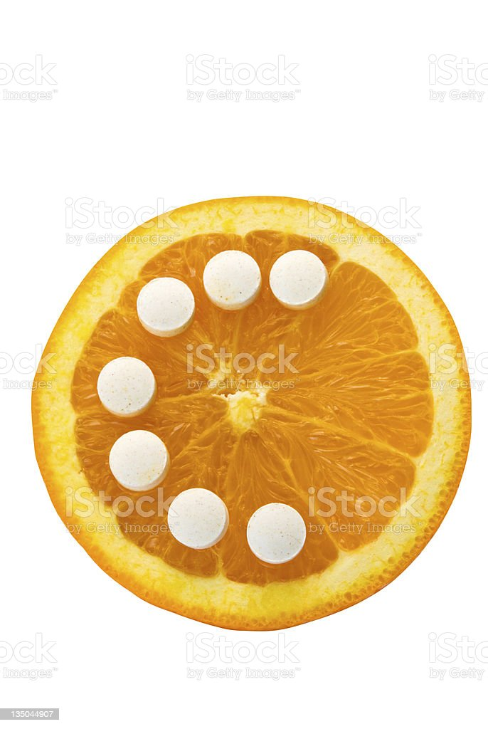 Orange half with Vitamin C pills forming the letter C stock photo