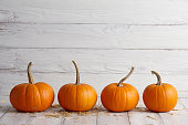 Orange halloween pumpkins on white planks