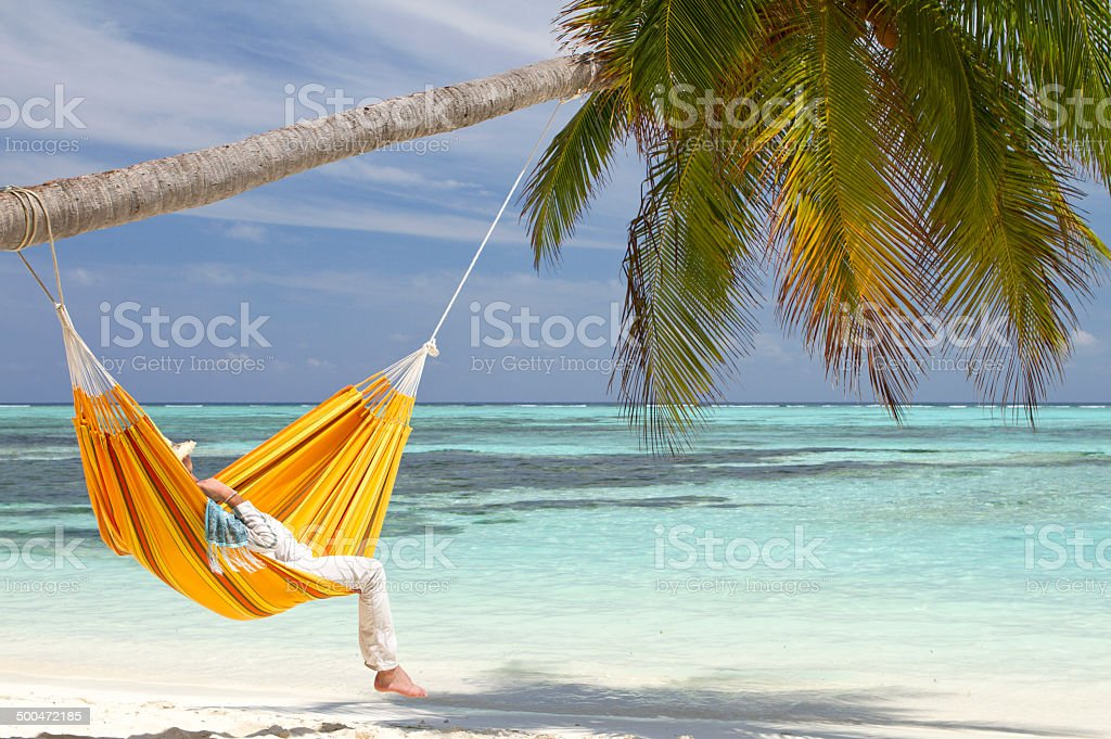 Orange hammock hanging on a paradise beach stock photo