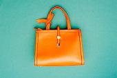 エメラルド グリーンの背景にオレンジ色のハンドバッグ