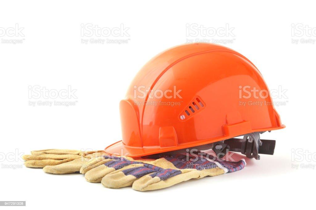 Orange hard hat, safety gloves on white background. Safety helmet. stock photo