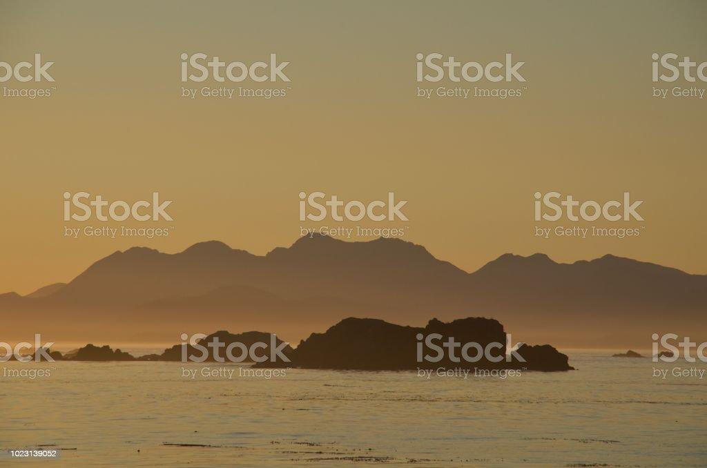 Orange Haze Of Setting Sun Makes Silhouettes Of Mountains Of