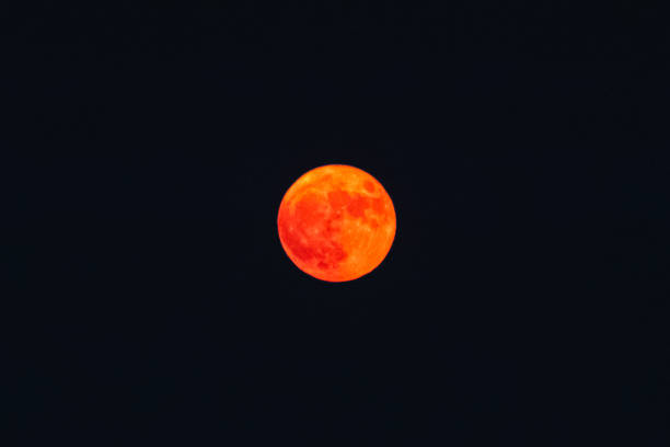 Orange haze over blurry red full moon, low visibility from wildfires smoke, San Francisco, California, United States stock photo