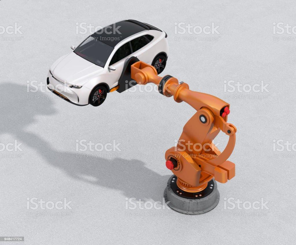 Orange heavyweight robotic arm delivering white SUV on concrete ground stock photo