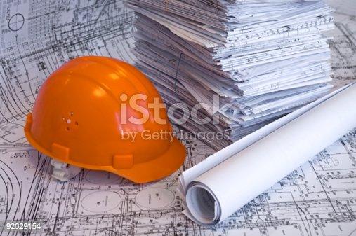 istock Orange helmet and heap of project drawings 92029154
