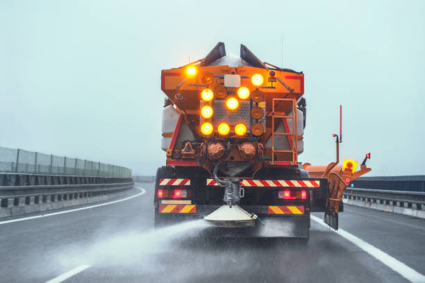 Orange highway maintenance gritter truck spreading de-icing salt on road in winter. stock photo
