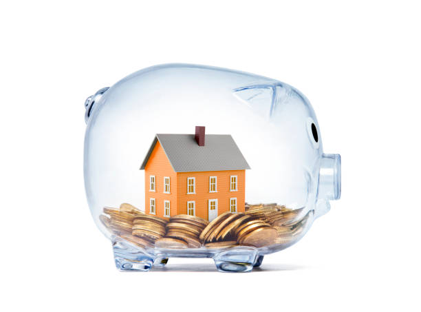 Orange house on money inside transparent piggy bank with clipping path stock photo