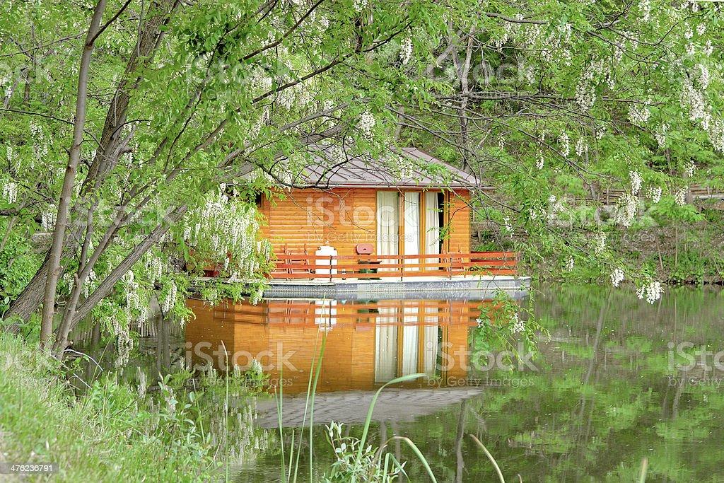 orange house on the calm lake surface and green sarounding royalty-free stock photo