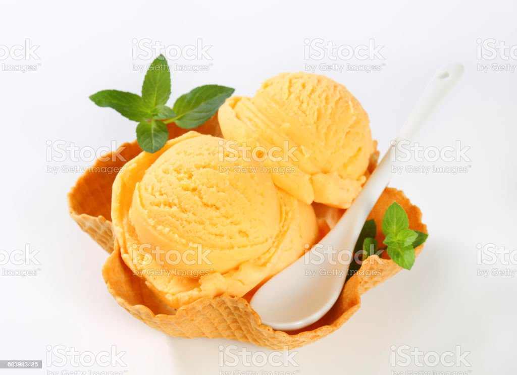 orange ice cream in a waffle basket stock photo