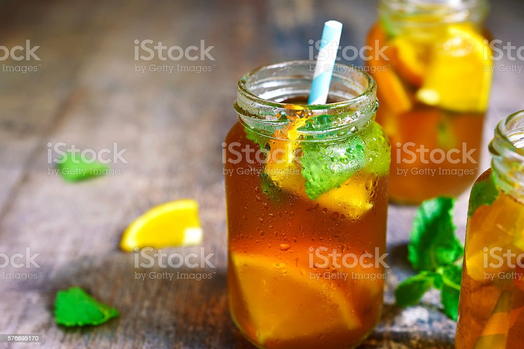 Orange iced tea in a glass jar with paper straws. stock photo