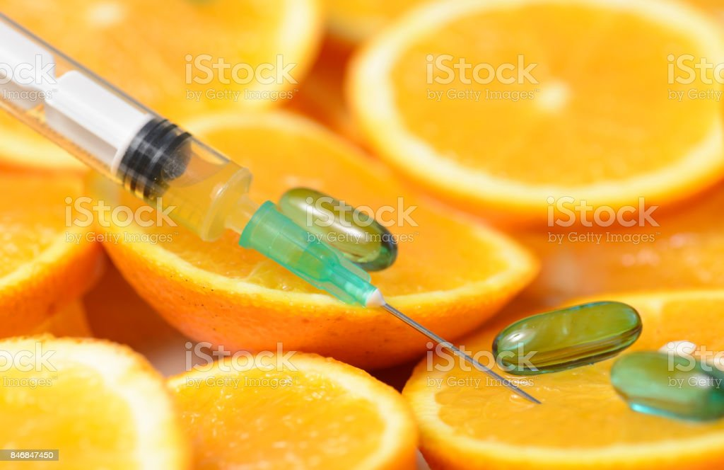 Orange in a Cut and a Syringe With Vitamin C stock photo