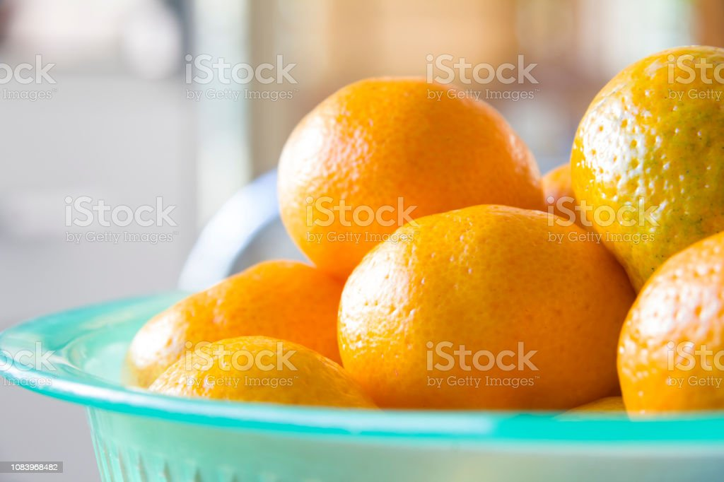 orange in light green basket stock photo