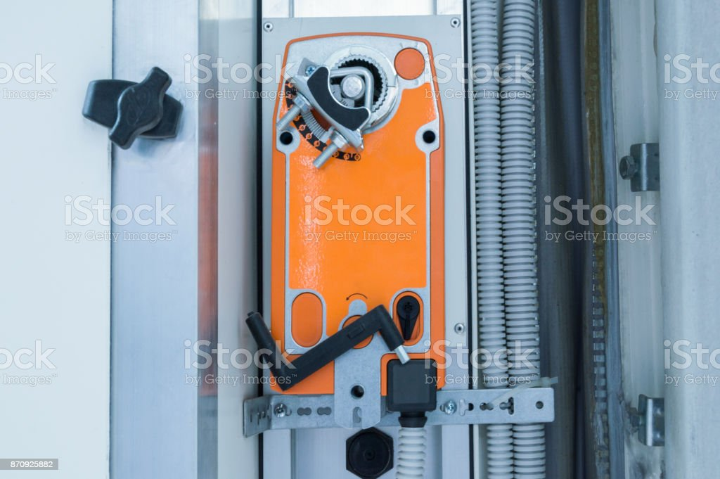 Orange industrial actuating motor nstalled on the industrial ventilation unit body, front view stock photo