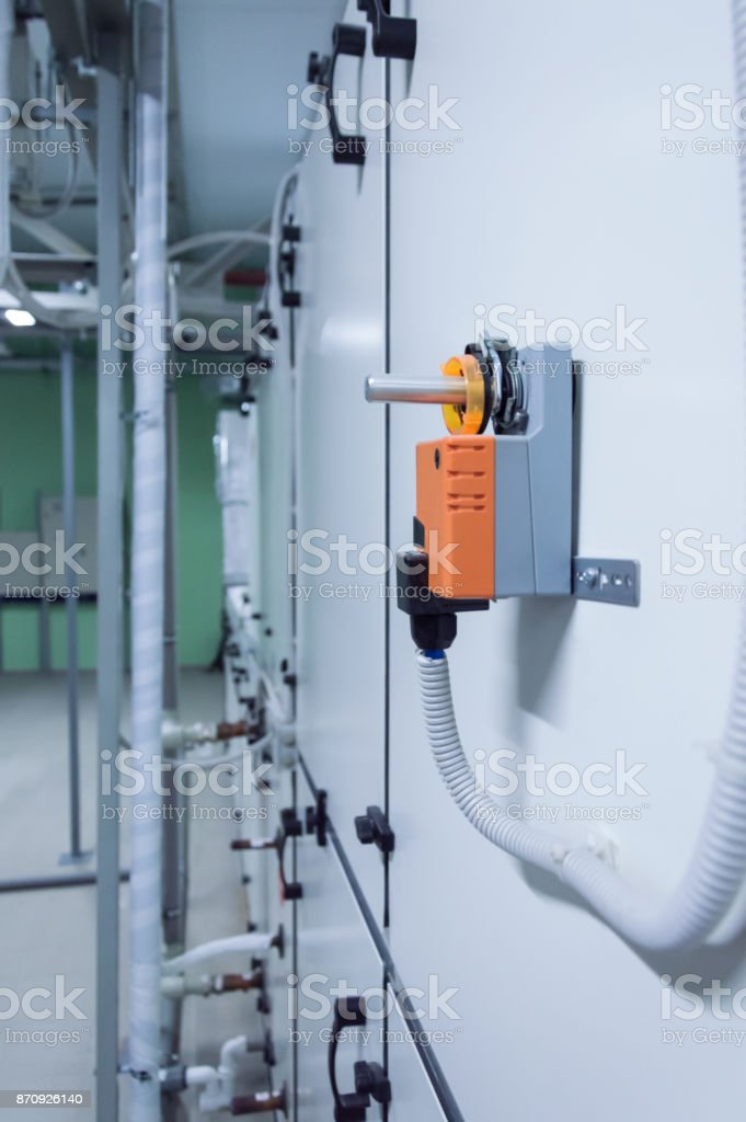 Orange industrial damper actuator nstalled on the industrial gray ventilation unit body. Side view stock photo