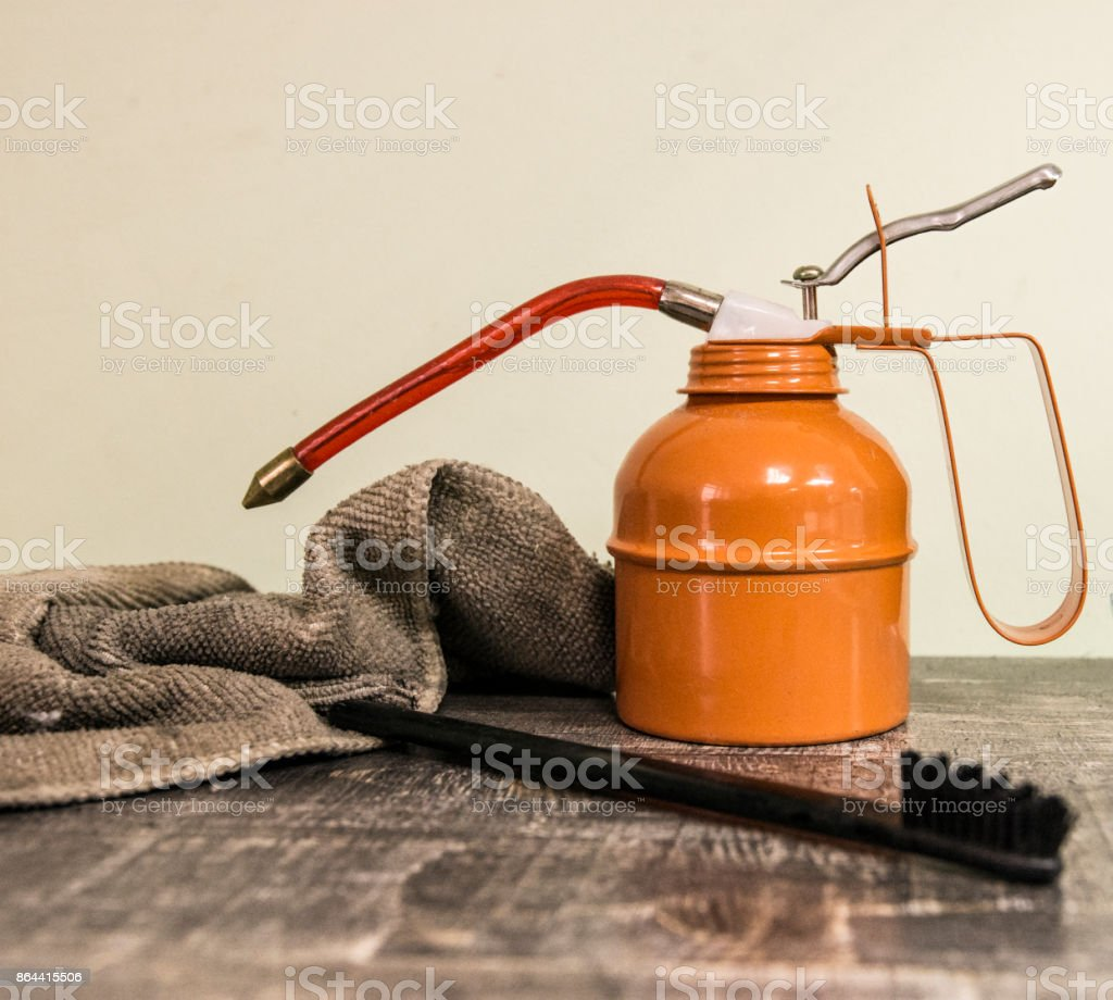 orange industrial oiler on a large table next to the brush and rag stock photo
