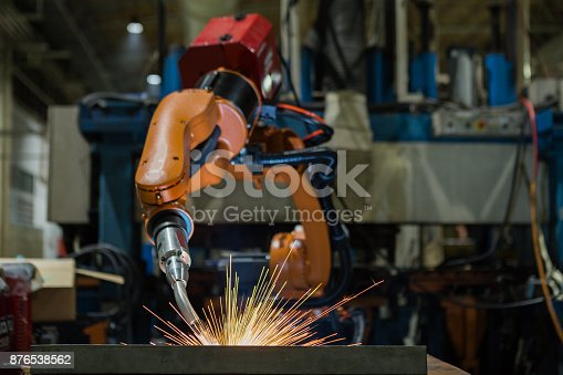 693576566 istock photo Orange industrial robot is welding assemblycar part in factory 876538562