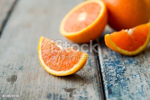 istock orange isolated on wood background 614873110