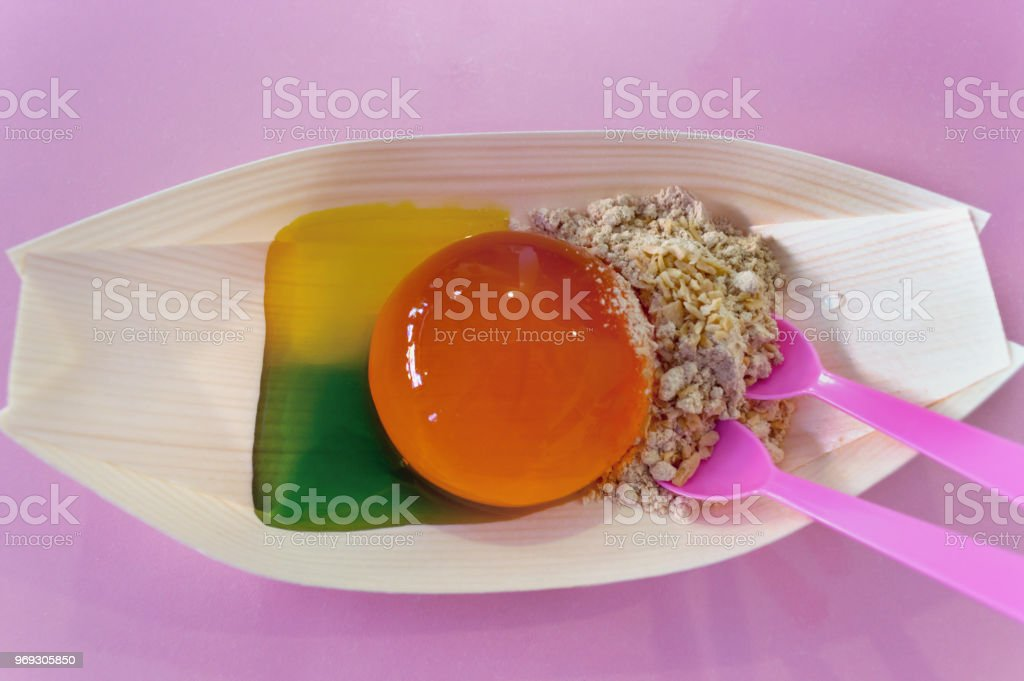 orange jelly drop made of marine algae with syrup and nuts dessert stock photo