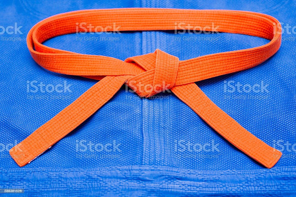 Orange judo belt on blue kimono stock photo