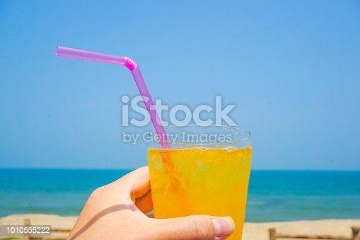 Orange juice drinking on the beach.