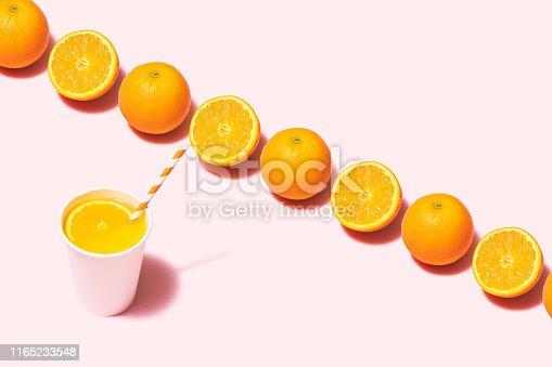 Orange juice and oranges flat lay on pink background