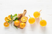 istock Orange juice. Freshly squeezed juice in glasses and fresh fruits with leaves, view from above 1182128307