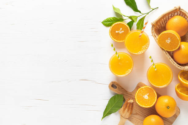 Orange juice. Freshly squeezed juice in glasses and fresh fruits with leaves, view from above stock photo