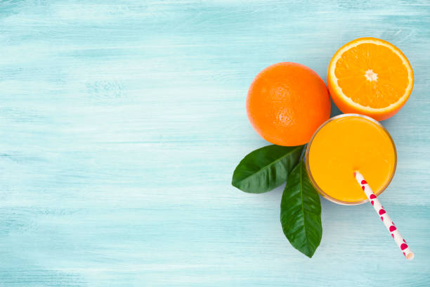 Orange juice glass and fruits on blue wooden tropical background stock photo