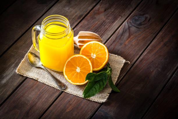 portakal suyu cam kavanoz rustik ahşap masaya vurdu - meyve ve sebze suyu soğuk i̇çecek stok fotoğraflar ve resimler