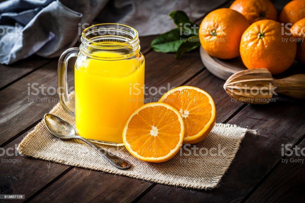 Orange juice glass jar shot on rustic wooden table