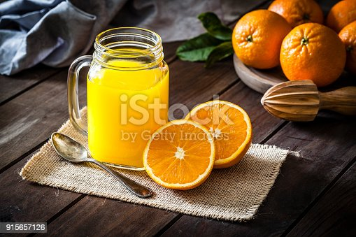 Orange juice glass jar shot on rustic wooden table. The jar is on a burlap cloth and two orange halves are beside it. An old metal spoon and a wooden juicer complete the composition. A round wooden tray with fresh oranges is at the top-right corner of an horizontal frame. Predominant colors are orange and brown. DSRL studio photo taken with Canon EOS 5D Mk II and Canon EF 100mm f/2.8L Macro IS USM