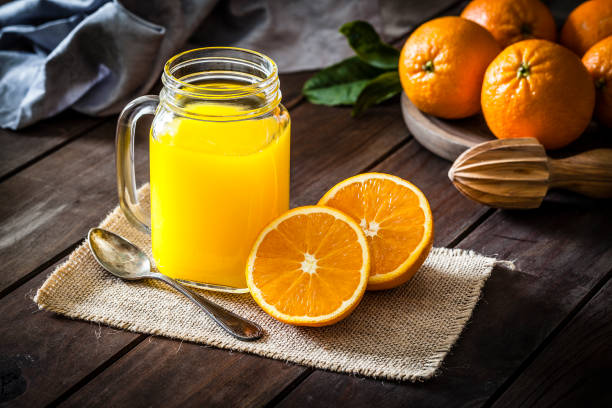 Orange juice glass jar shot on rustic wooden table stock photo