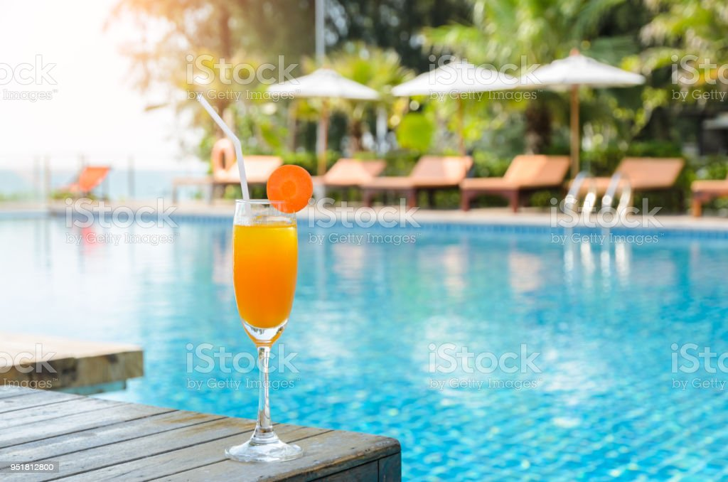 Glas Orangensaft auf Holztisch mit Schwimmbad Blick Hintergrund – Foto