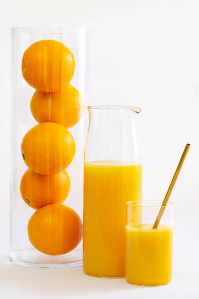 Orange juice in a glass and a jug with a gold metal straw by a tall glass tube full of oranges over a white background. Vertical view. stock photo